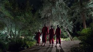 En rödklädd familj ser hotfull ut där alla fyra står hand i hand.