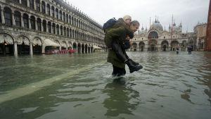 En man bär en kvinna över en översvämmad Piazza San Marco i Venedig.