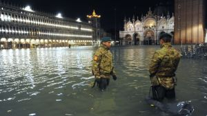 Två poliser vadar i vattnet på en översvämmad Piazza San Marco i Venedig.