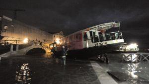 En vattenbuss som ligger på sin sida i en översvämmad kanal i Venedig.