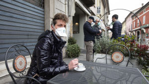 En man med skyddsmask på ett café i Codogno, Lombardiet på måndagen. Codogno är en av de värst drabbade orterna.
