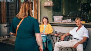 Anna Airola, Elias Salonen ja Anna Dahlman katsovat toisiaan AIKUISET-sarjan kahvilan edessä.