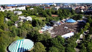 Ilmakuva Tuska-festivaalin aikaan Helsingin Kaisaniemestä, jossa festivaalitelttoja ja suuri yleisöjoukko.