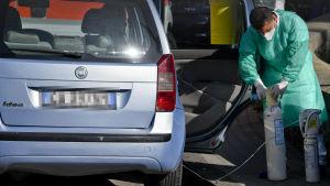 Syrgas transporteras till en person inne i en bil i Neapel,  Italien 9.11.202