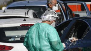 Person med covid-19-symptom får behandling inne i en bil i Neapel, Italien 9.11.2020