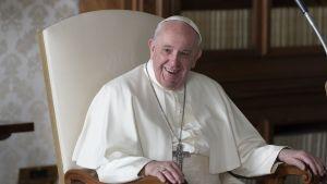 Påven Franciskus sitter på en stol och skrattar