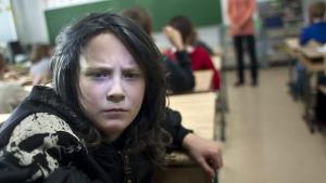 kovispoika katsoo kameraan luokassa