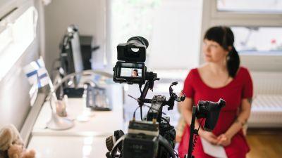 Punamekkoinen nainen istuu kameran edessä kuvaustilanteessa