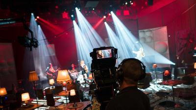 Kuva studion kulisseista, kameramies etualalla.