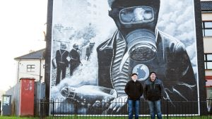 Kaksi miestä seisoo ison kaasunaamarimaalauksen edessä.