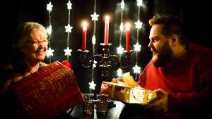 Pia Abrahamsson och Stan Saanila vid en ljusstake och med presenter i händerna.