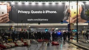 Kravallpolis står framför en stor iphone-reklamskylt