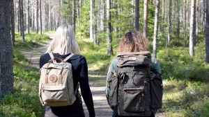 Fotade bakifrån går Marina och Lina i en grön skog med ryggväskor.