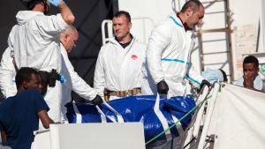En liksäck med en död migrant bärs i land av den italienska kustbevakningen.