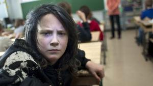 Mustahiuksinen poika istuu luokassa ja katsoo kameraan poispäin opettajan taulusta. Ilme on synkkä.