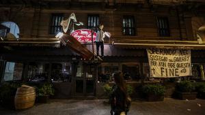 """En restaurang i Neapel protesterar mot den italienska regeringens restriktioner med att hänga två dockor och en likkista utanför restaurangen. En banderoll utanför restaurangen lyder: """"Vi hoppas att regeringen hjälper oss så att det inte ska så här illa"""""""