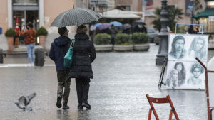 Ett påar promenerar i regnet i Rom