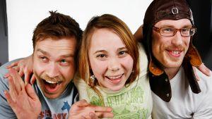 Magnus, Carina och Petski. Ser glada ut. Kramas. Petski har en flygarmössa på sig.