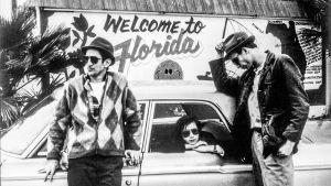 mustavalkeassa kuvassa kaksi miestä nojailee autoon ja nainen istuu auton sisällä ja katsoo ulos ikkunasta.