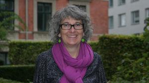 Glad, vit kvinna med grått lockigt hår och glasögon står framför tegelhus.