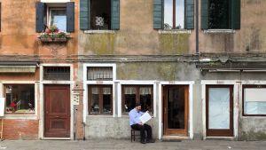 Mies istuu talon edessä ja lukee lehteä.