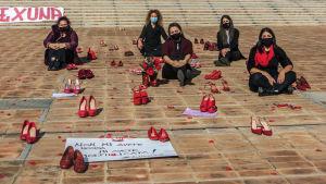Engrupp kvinnor sitter på ett torg och har lagt ut röda damskor omkring sig.