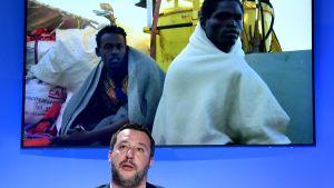 Italiens inrikesminister Matteo Salvini framför en bild av Medelhavsflyktingar.