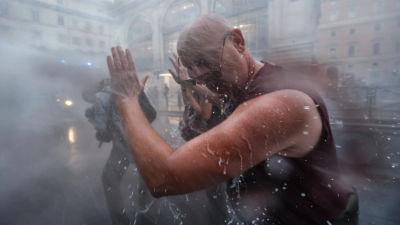 Man blir beskjuten med vattenkanon i ansiktet under en demonstration.