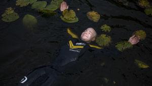 Juha Riikonen kelluu märkäpuku päällä vedessä lumpeiden seassa.