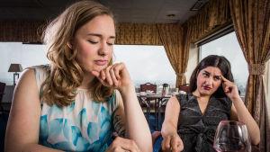 Dilan och Moa sitter med sura miner på en restaurang.