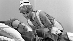 Scen ur filmen Persona med sjuksköterska och patient i en säng.