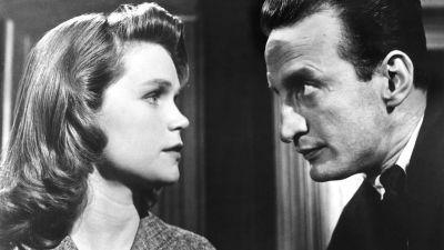 Nainen (Lee Remick) ja mies (George C. Scott) tuijottavat toisiaan tiiviisti oikeussalissa. Kuva elokuvasta Erään murhan anatomia