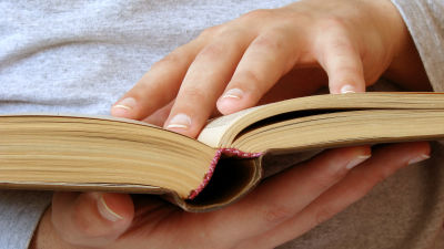 Händer håller i öppen bok