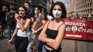 Demonstration i Milano. Två unga kvinnor i förgrunden.