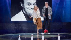 Sanna Stellan potkii keilapalloja pallolla ja Marco Bjuström seuraa vierestä.