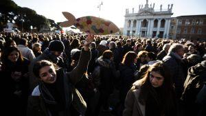 En stor folksamling på ett torg i Rom, en person i förgrunden med en sardin gjord av papp i handen.
