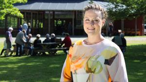 Programledare Mette Bluhme Rieck står i solen på en gräsmatta.