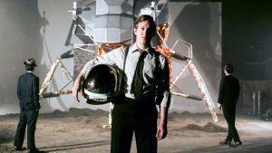 Mies seisoo kuvattavana avaruuskypärä kainalossaan.
