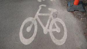 En bild av en cykel som målats på asfalten på en cykelväg
