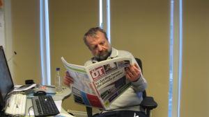 En man sitter vid ett skrivbord och läser Österbottens tidning.