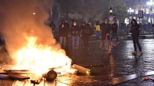 En del av demonstranterna i en protest mot coronarestriktioner i den italienska staden Turin bränner bråte på gatan.