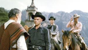 Yul Brynner elokuvassa Seitsemän rohkeaa miestä. Selin Vladimir Sokoloff. Taustalla Horst Buchholz ja Steve McQueen