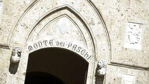 Ingången till banken Monte dei Paschi di Siena i Italien, med texten Monte dei Paschi skrivet.