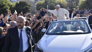 Påve Franciskus lägger sin hand på ett barns huvud under sitt besök i Palermo.