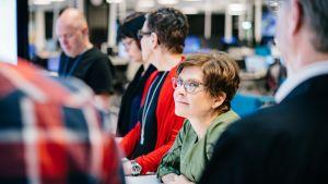 Miehiä ja naisia palaverissa pöydän ääressä Yle Uutisissa