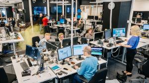 Ihmisiä työskentelee uutishuoneessa.
