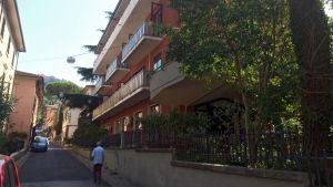 Nelikerroksinen, parvekkeellinen hotellirakennus kapean kadun varrella Italiassa.
