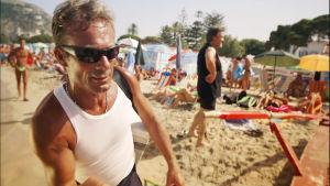 Mies hihattomassa paidassa rannalla, jossa paljon ihmisiä.