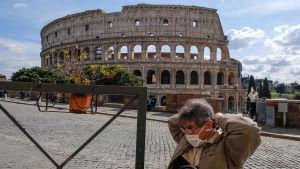 Man med munskydd framför Colosseum i Rom