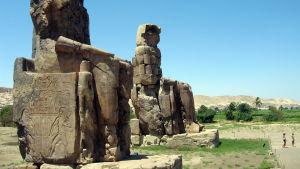 Två gigantiska egyptiska statyer i ett ökenlandskap.